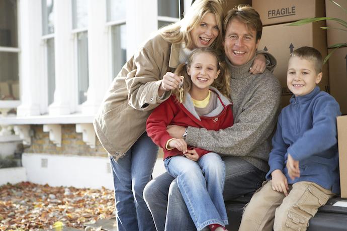 Family sitting in back of van holding keys, smiling, portrait